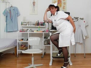 Mature woman wearing a nurse outfit plays with her snatch