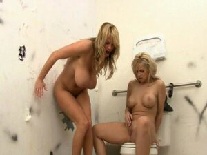 Sarah and Kelly are in the mood for some dirty fucking in a bathroom stall with a gloryhole cock to suck