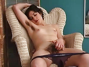 A sexy chick lays naked on her own and plays with her hairy fur burger