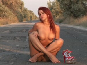Redhead walks the road in only heels