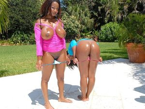 Two smoking hot ebony babes cover themselves in oil out in the sun and rub each other sexily
