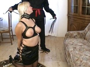 Busty blonde slave is tied up and on the floor blowing master's rod