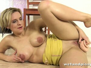 Blonde MILF moans while rolling around in a puddle of her piss
