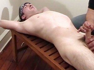 A dude is wanking off a tied up guys cock