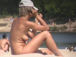 Beach nudist girl talks on phone and gets voyeured