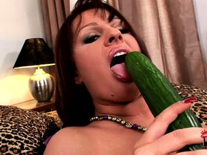 Busty brunette MILF fucks herself deep with a thick cucumber