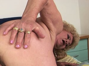 Big-tittied granny rides on a young babe's massive strap-on dildo